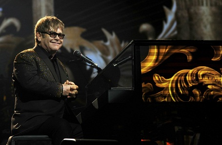 Elton John smiling on his new million dollar piano